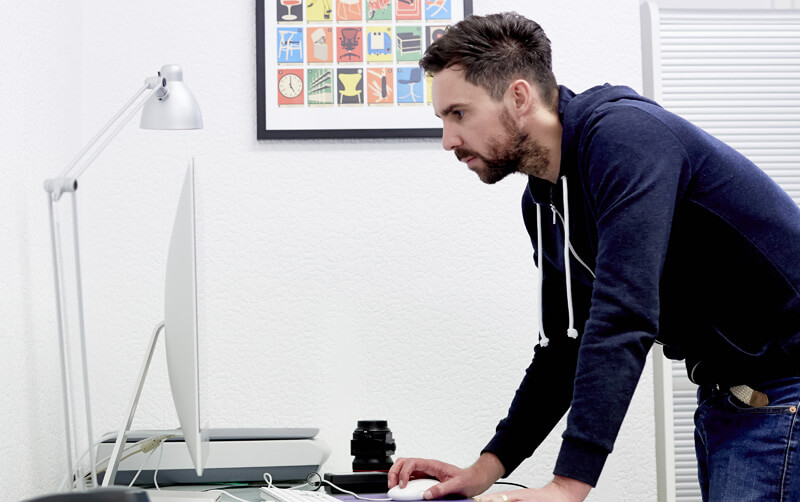 Mark Smith Graphic Designer standing at desk using mouse looking at screen